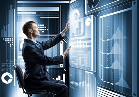 Young businessman sitting on chair and working with virtual panel Фото со стока