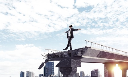 Businessman walking blindfolded on concrete bridge with huge gap as symbol of hidden threats and risks. Cityscape and sunlight on background. 3D rendering. Stock Photo