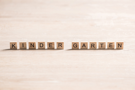 Alphabet letters on wooden pieces collected to word kinder garten