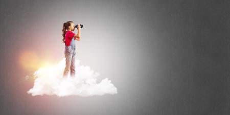 Cute kid girl standing on cloud and looking in binoculars