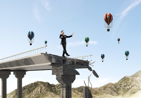 Businessman walking blindfolded on concrete bridge with huge gap as symbol of hidden threats and risks. Flying balloons and nature view on background. 3D rendering. 写真素材