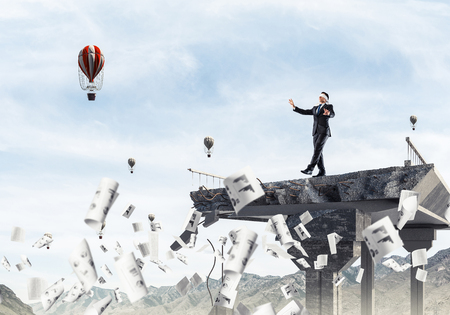 Businessman walking blindfolded among flying documents on concrete bridge with huge gap as symbol of hidden threats and risks. Flying balloons and nature view on background. 3D rendering. 写真素材