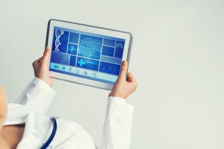 医者の手で医学インターフェイス画面とタブレット pc デバイス