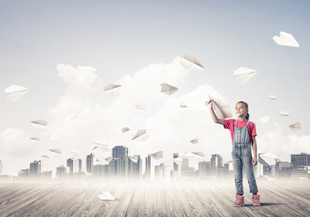 careless: Cute kid girl stand on wooden floor and paper planes flying around Stock Photo
