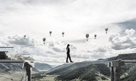 歩くビジネスマンは隠された脅威とリスクのシンボルとして橋の巨大なギャップの上のロープを目隠し。空飛ぶ風船と自然観の背景。3 D レンダリン