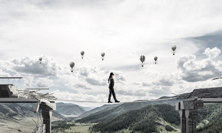 Businessman walking blindfolded on rope above huge gap in bridge as symbol of hidden threats and risks. Flying balloons and nature view on background. 3D rendering. Stock Photo