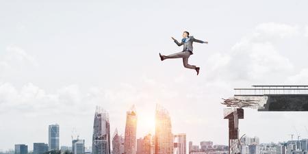 El hombre de negocios saltando sobre la enorme brecha en el puente de hormigón como símbolo de la superación de los desafíos. Paisaje urbano con luz del sol en el fondo. Representación 3D