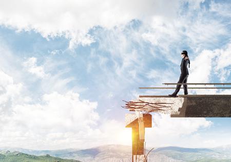 歩くビジネスマンは隠された脅威とリスクのシンボルとして巨大なギャップを持つコンクリート橋に目隠し。空の景色と自然を背景に表示します。3  写真素材