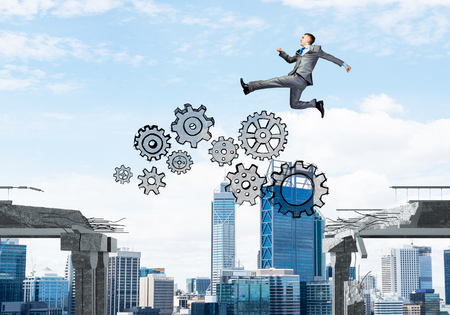 Businessman jumping over gap with gear mechanism in concrete bridge as symbol of overcoming challenges. Cityscape on background. 3D rendering. Stock Photo