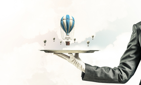 Closeup of waitresss hand in glove presenting flying aerostats on metal tray with blue cloudy skyscape on background. 3D rendering.