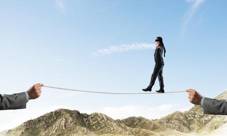 Empresario caminando con los ojos vendados en la cuerda sobre las altas montañas como símbolo de amenazas ocultas y apoyo. Skyscape y vista de la naturaleza en el fondo.