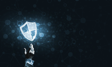 Person touching shield glowing icon as concept about security and protection 스톡 콘텐츠