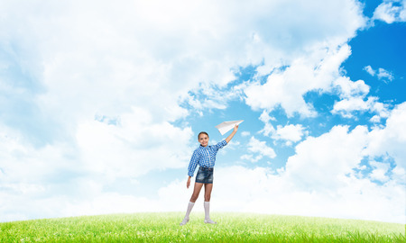 Adorable little girl holding a paper plane outdoors on green grass