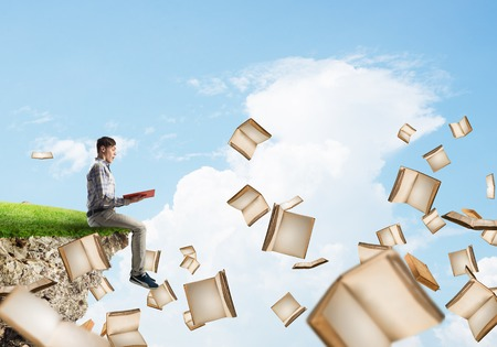 Young man floating on island in blue sky with red book in hands