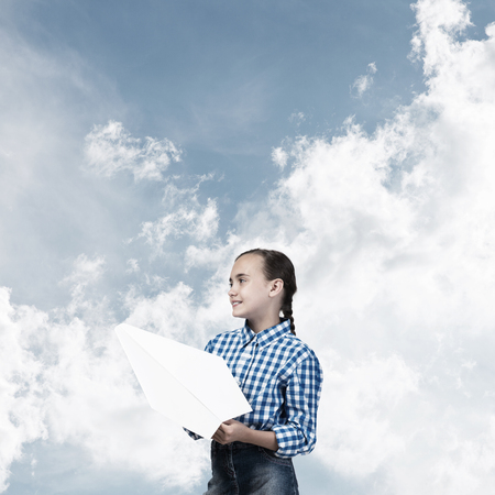 Adorable little girl holding paper plane outdoors on blue sky background