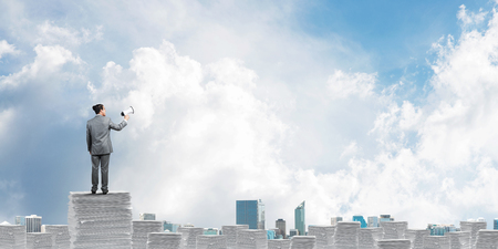 Businessman in suit standing on pile of documents with speaker in hand with skyscape and city view on background. Mixed media. Stock Photo
