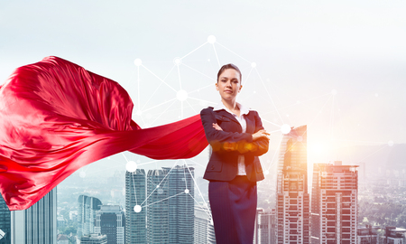Young confident businesswoman wearing red cape against modern city background Фото со стока - 87640159