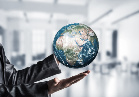 Cropped image of business woman in suit holding Earth globe in hands with office view on background. Elements of this image are furnished by NASA. Stock Photo