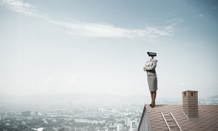 head protection: Faceless businesswoman with camera zoom instead of head standing on house roof Stock Photo