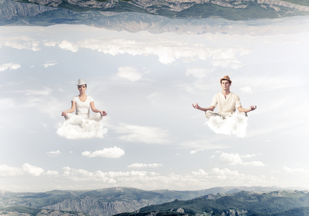 Young couple keeping eyes closed and looking concentrated while meditating on clouds in the air between two nature worlds.