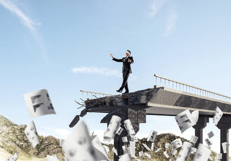 Businessman walking blindfolded among flying documents on concrete bridge with huge gap as symbol of hidden threats and risks. Skyscape and nature view on background. 3D rendering. 写真素材
