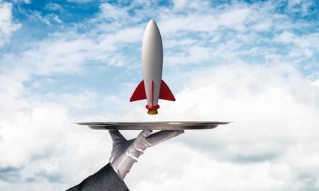 웨이트리스 자른 된 이미지 배경에 흐린 skyscape와 금속 트레이에 비행 미사일을 제시하는 흰 장갑에 손을. 스톡 콘텐츠