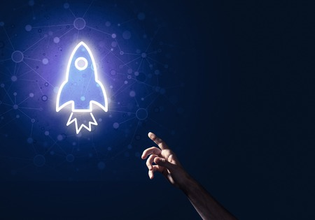 Rocket glowing icon and man hand on dark background