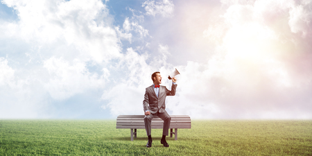 Young businessman sitting on bench and screaming emotionally in megaphone Stock Photo