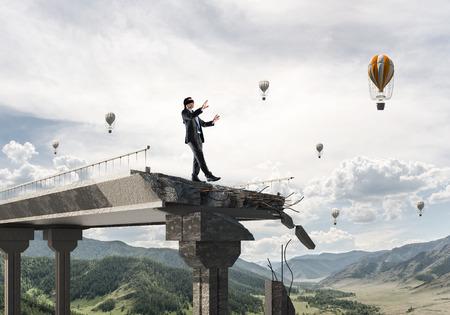 Empresario caminar con los ojos vendados en el puente de hormigón con enorme espacio como símbolo de amenazas y riesgos ocultos. Globos voladores y vista de la naturaleza en el fondo. Representación 3D Foto de archivo