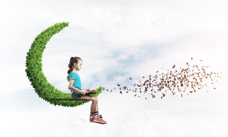 Cute kid girl sitting on moon in day sky and reading book Stock Photo