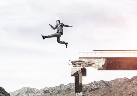 El hombre de negocios saltando sobre la enorme brecha en el puente de hormigón como símbolo de la superación de los desafíos. Skyscape y vista de la naturaleza en el fondo. Representación 3D.