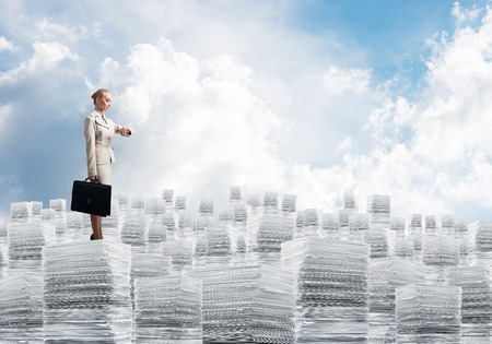 law suit: Confident business woman in suit standing on pile of documents with cloudly skyscape on background. Mixed media.