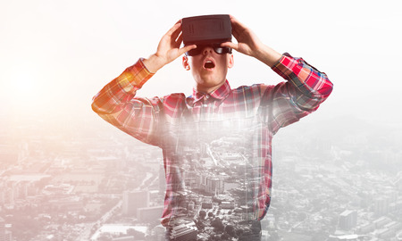 modified: Young man with virtual reality headset or 3d glasses over cityscape background