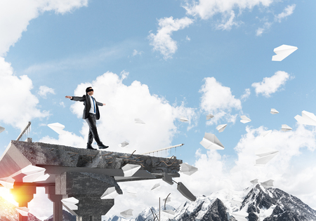 Empresario caminando con los ojos vendados entre volar aviones de papel en el puente de hormigón con gran brecha como símbolo de amenazas y riesgos ocultos. Skyscape y vista de la naturaleza en el fondo. Representación 3D
