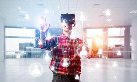 Young man with virtual reality headset or 3d glasses over social connection background . Mixed media Stock Photo