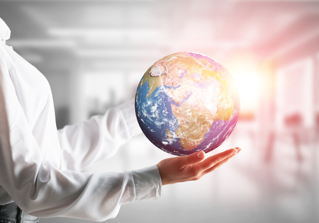 Side view closeup of business woman in shirt holding Earth globe in hands with sunlight and office view on background. Elements of this image are furnished by NASA.