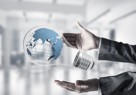 Cropped image of business woman hands holding lightbulb with Earth globe inside with office view on background. Mixed media.