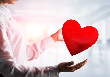 Cropped image of business woman in shirt keeping big red heart in his hands with office view and sunlight on background. Mixed media. Imagens