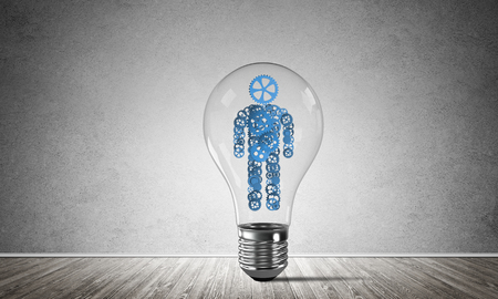 Glass lightbulb with human from gears inside placed in empty room with grey wall on background. 3D rendering.