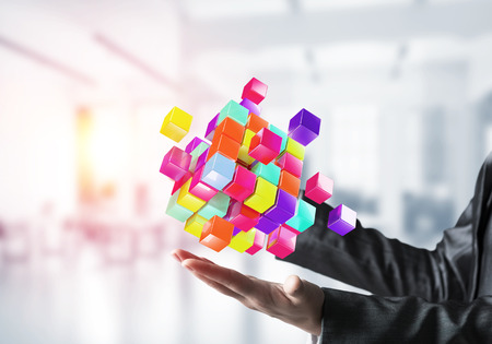 Closeup shot of business woman hands holding multiple cubes of different colours in hands with sunlight on office background. Mixed media. Stock Photo