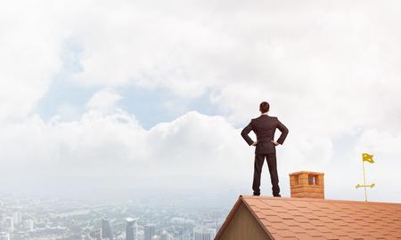 젊은 사업가 집 지붕에 서서 멀리 찾고 결정. 혼합 매체 스톡 콘텐츠
