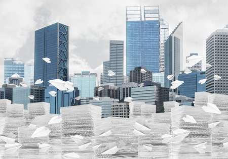 Horizontal shot of flying paper planes and piles of documents with cityscape on background. Mixed media.