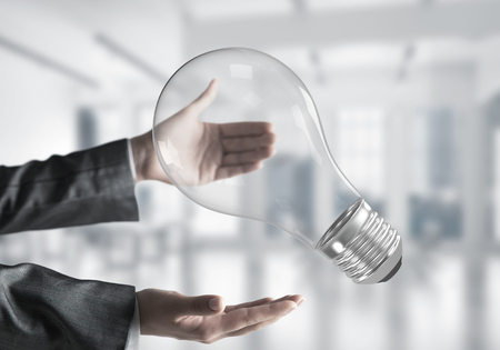Closeup shot of business woman hands holding lightbulb with office view on background. Mixed media.