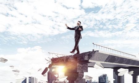 Empresario caminando con los ojos vendados entre volar aviones de papel en el puente de hormigón con gran brecha como símbolo de amenazas y riesgos ocultos. Paisaje urbano y luz del sol en el fondo. Representación 3D