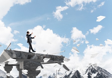 Businessman walking blindfolded among flying paper planes on concrete bridge with huge gap as symbol of hidden threats and risks. Skyscape and nature view on background. 3D rendering. 写真素材