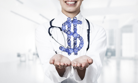Close of woman doctor showing in palm gear made dollar sign