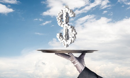 Cropped image of waitresss hand in white glove presenting multiple cubes in form of dollar sign on metal tray with cloudy skyscape on background. Reklamní fotografie