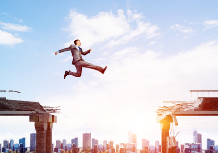 Businessman jumping over gap with flying letters in concrete bridge as symbol of overcoming challenges. Cityscape with sunlight on background. 3D rendering. Imagens - 88145579