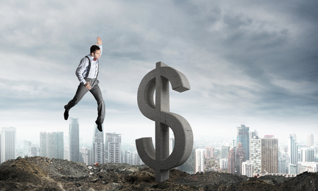 Springende zakenman in slimme vrijetijdskleding die groot dollarsymbool met stadsmening verpletteren op achtergrond.