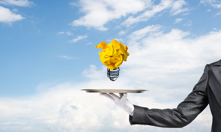 Cropped image of waitresss hand in white glove presenting crumpled paper lightbulb on metal tray with cloudy skyscape on background.
